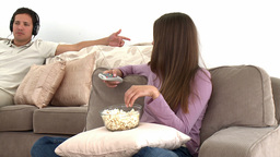 Girl watching tv with popcorn while her boyfriend  Footage