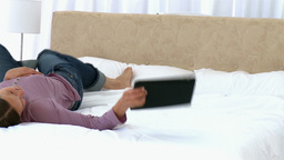 Woman using a tablet lying on the bed Stock Video Footage