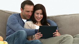 Happy couple using a computer tablet sitting on th Footage