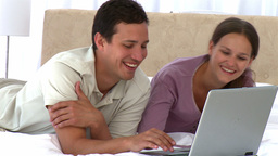 Happy couple looking at the laptop while lying on Stock Video Footage