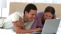 Happy couple looking at the laptop while lying on  Footage