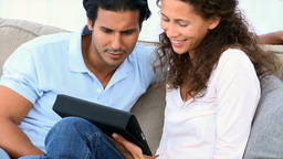 Couple using a computer tablet sitting on the couc Footage