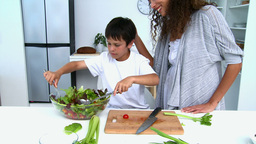 Boy cooking a salad with his mother Footage