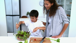 Boy cooking a salad with his mother Stock Video Footage