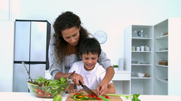 Mother cooking a salad with her son Footage