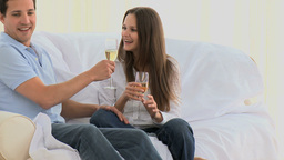 Man and his wife drinking sitting on the sofa Stock Video Footage