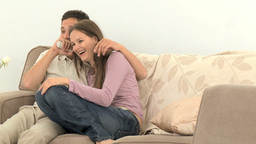 Lovely couple watching television sitting on the s Footage