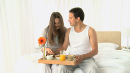 Lovely couple having breakfast sitting on the bed Stock Video Footage
