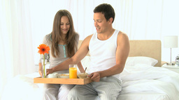 Beautiful couple having breakfast sitting on the bed Footage