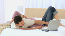 Woman lying on her boyfriend while he is working on his laptop Footage