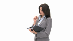 Pensive businesswoman writing on her agenda Footage