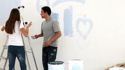 Couple painting a wall in blue Footage