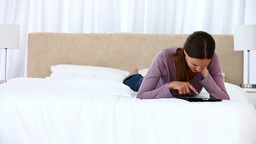 Happy woman using a computer tablet lying on the b Footage