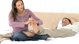Beautiful woman massaging his husbands feet Footage