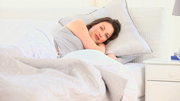 Beautiful woman lying in the bed and looking at th Stock Video Footage
