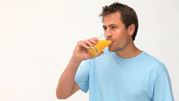 Man drinking a glass of orange juice Footage
