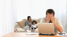 Angry man on his laptop while his family is on a sofa Live Action