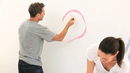Young couple painting a wall together Footage