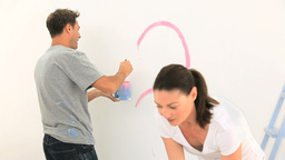 Young couple painting a wall together Stock Video Footage