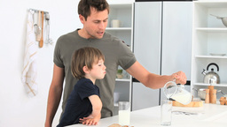 A dad serving a glass of milk to his son Stock Video Footage