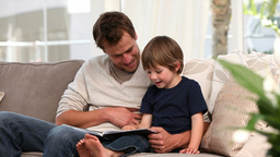Nice father reading a story to his young son Footage