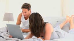 Pretty woman on her laptop while her husband is re Footage