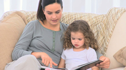 A mother reading a story to his daughter Stock Video Footage