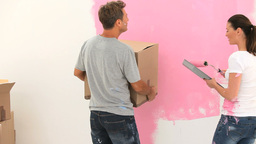 Young woman painting a wall and talking with her h Footage