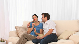 Smiling couple on a sofa with a red rose Footage