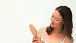 Woman brushing her hair in front of the mirror Footage