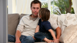 Attentive father watching tv with his son Stock Video Footage