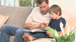 Man reading a book with his son Stock Video Footage