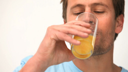 Man drinking orange juice Footage
