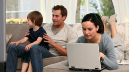 Woman using laptop while her boy and husband are w Footage