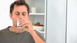 Handsome man drinking a glass of milk Footage