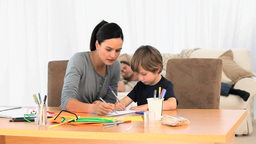 Attentive Mother Drawing With Her Son While Father stock footage