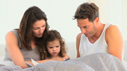 Family reading a book sitting on the bed Stock Video Footage
