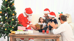 Distribution of gifts by Santa Claus to a family Footage