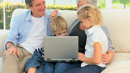 Family laughing in front of a computer Footage