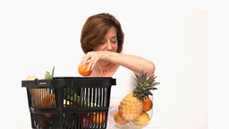 Mature woman putting fruit into a bowl Footage