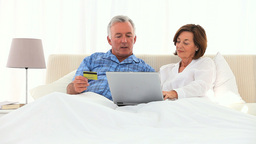 Elderly couple using a credit card on the internet Footage