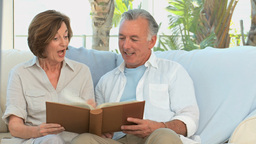 Aged couple looking at a photos album Footage