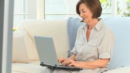 Elderly woman working on her laptop Footage