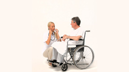 Man in a wheelchair talking to his nurse Footage