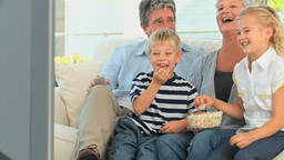 Family watching tv while eating popcorn Stock Video Footage