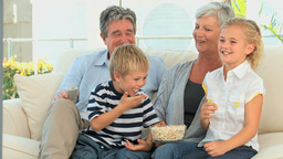 Family watching tv while eating popcorn Footage