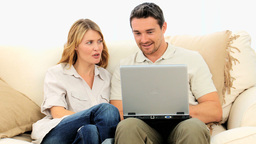 Lovely couple using a laptop Stock Video Footage