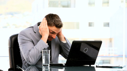 Young businessman despairing in front of his laptop Live Action