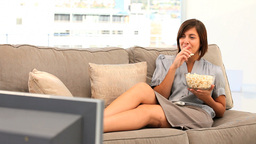 Pretty lady watching tv with popcorn Stock Video Footage