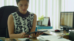 Young Asian Office Worker With a Tablet At Her Des Footage